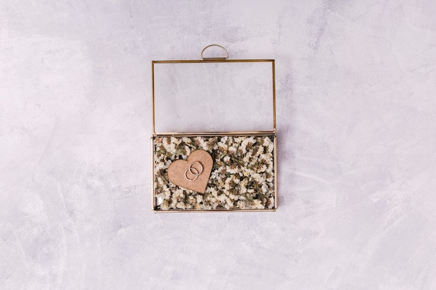 Bagues en coeur d'ornement entre fleurs en boite Photo gratuit