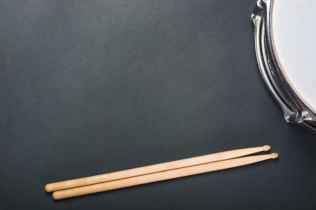 Baguettes en bois et tambour sur fond noir Photo gratuit