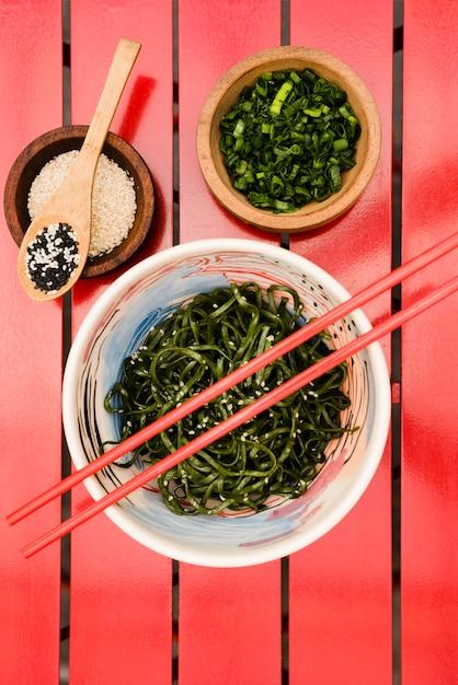 Des baguettes sur la salade d'algues chuka japonaise servie avec des graines de sésame et des oignons nouveaux hachés sur une table rouge Photo gratuit