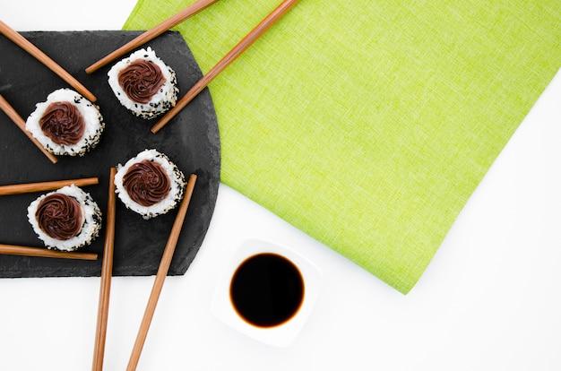 Baguettes avec sushi roule sur une plaque noire sur fond blanc et vert Photo gratuit