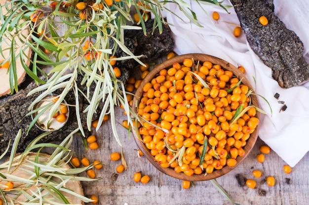 Baies d'argousier dans un bol sur une table en bois, vue de dessus Photo Premium
