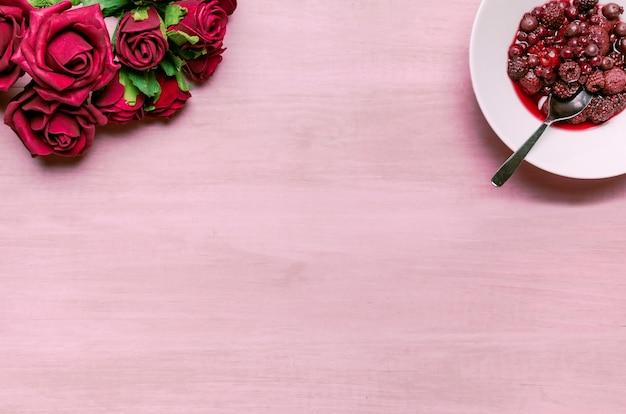 Baies sur assiette avec bouquet de roses rouges Photo gratuit