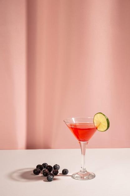 Baies bleues fraîches avec un cocktail sur un bureau blanc Photo gratuit