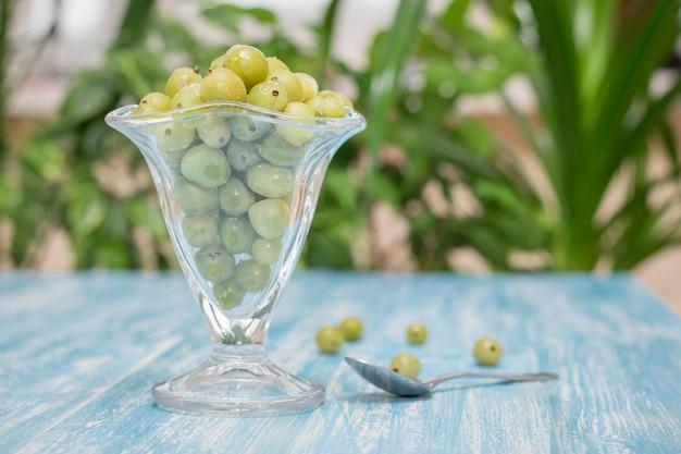 Baies congelées groseilles à maquereau dans un bol de verre sur la table vintage. Photo Premium