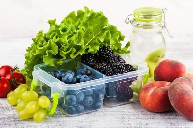 Baies dans une boîte à lunch et fruits Photo Premium