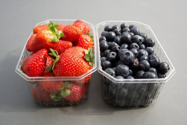 Baies dans un récipient en plastique. fraise fraîche et myrtille dans une boîte en plastique Photo Premium