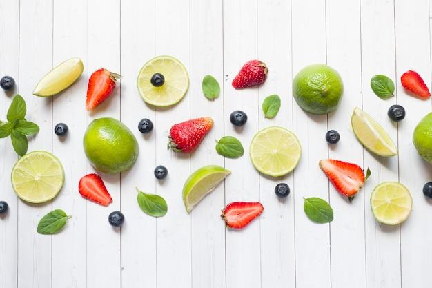 Baies fraîches d'agrumes citron vert menthe bleuets fraises sur un fond clair. Photo Premium