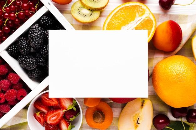 Baies fraîches à plat et fruits avec du papier Photo gratuit