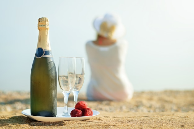 Baies Fraises Fraîches, Bouteille De Champagne, Verres Et La Femme Sur La Plage. Photo Premium