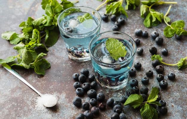 Baies et menthe autour de boissons rafraîchissantes à la myrtille Photo gratuit