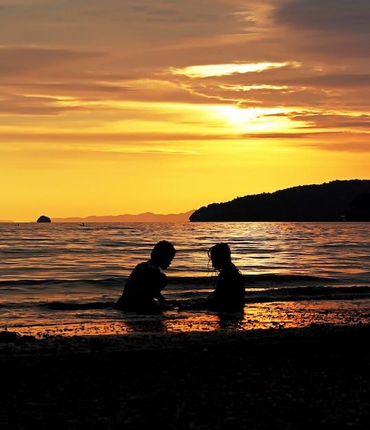Baigneurs au coucher du soleil Photo gratuit