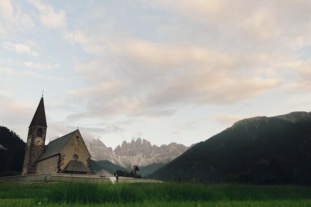 Baiser, mariage, couple, devant, pierre, église, dans montagnes Photo gratuit