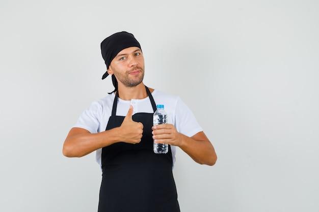 Baker Man Holding Bouteille D'eau, Montrant Le Pouce Vers Le Haut En T-shirt Photo gratuit