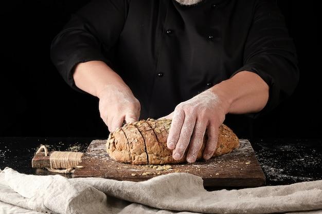 Baker en uniforme noir coupe un couteau en tranches de pain de seigle Photo Premium