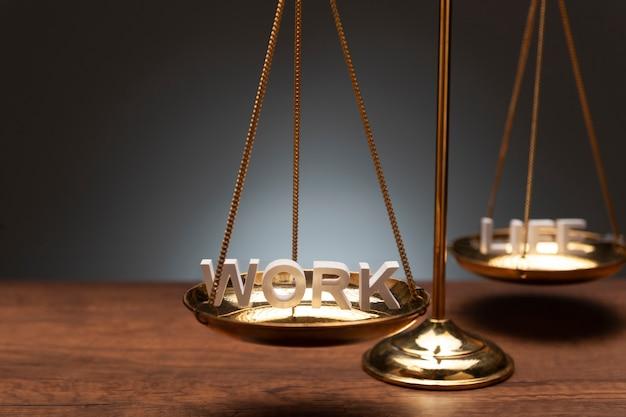 Balance en laiton doré sur bureau en bois et fond gris Photo Premium