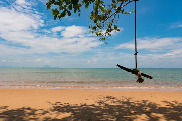 Balancer sur la branche d'arbre près de la plage, mer pendant la saison estivale. Photo Premium