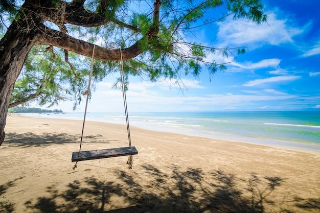 Balançoire en bois suspendue à un arbre sur la plage. Photo Premium