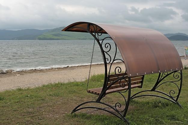 Balançoire forgée avec un toit au bord de la mer. Photo Premium