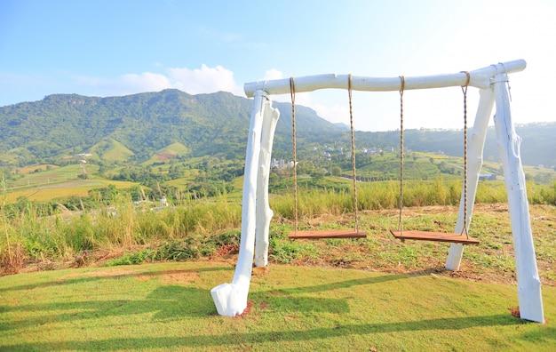 Balançoire vide sur la colline avec le lever du soleil du matin. Photo Premium