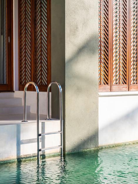 Balcon extérieur au bord de la piscine avec escalier et chaise Photo Premium
