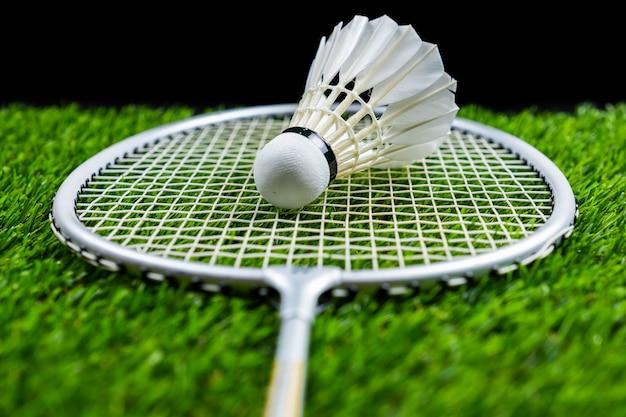 Balle de badminton et raquette sur l'herbe sur fond noir Photo Premium