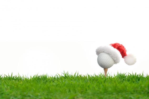 Balle de golf d'allure festive sur un tee-shirt avec le chapeau du père noël au sommet pour la saison des vacances, isolée on white Photo Premium