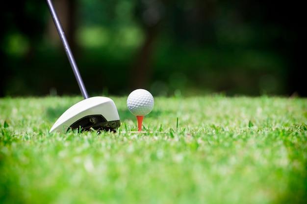 Balle de golf sur le tee devant le conducteur de golf sur un terrain vert Photo Premium