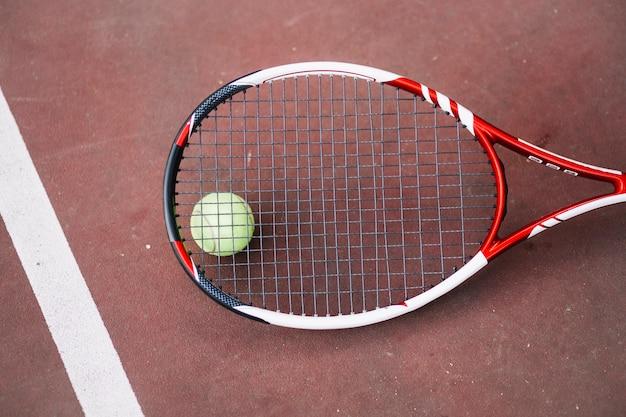 Balle de tennis à angle élevé avec une raquette à côté Photo gratuit