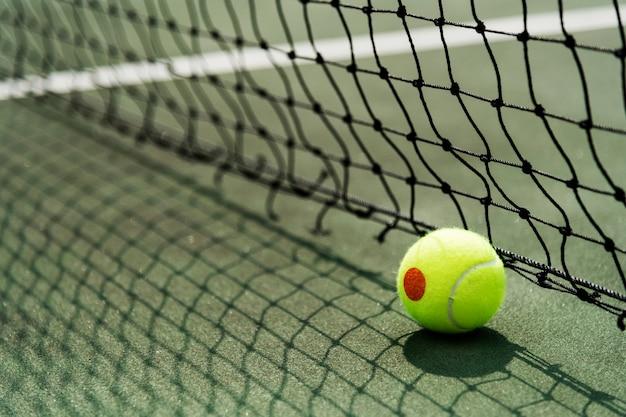 Balle de tennis sur un court de tennis Photo gratuit