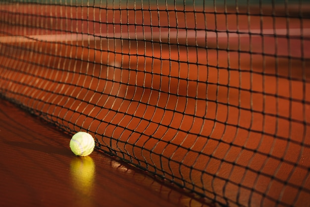 Balle de tennis près d'un filet de tennis Photo gratuit