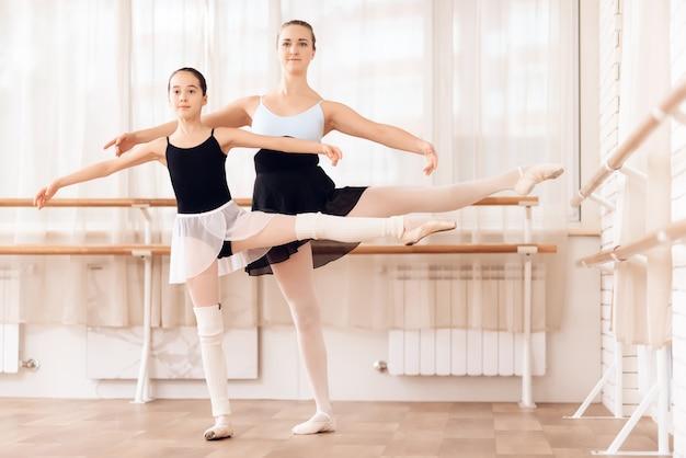 Une ballerine adulte et une ballerine dansent dans un gymnase. Photo Premium