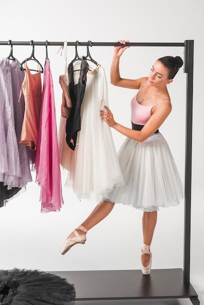 Ballerine, debout, sur, pointe pointe, choisir, tutu, depuis, cintres, contre, blanc, toile de fond Photo gratuit