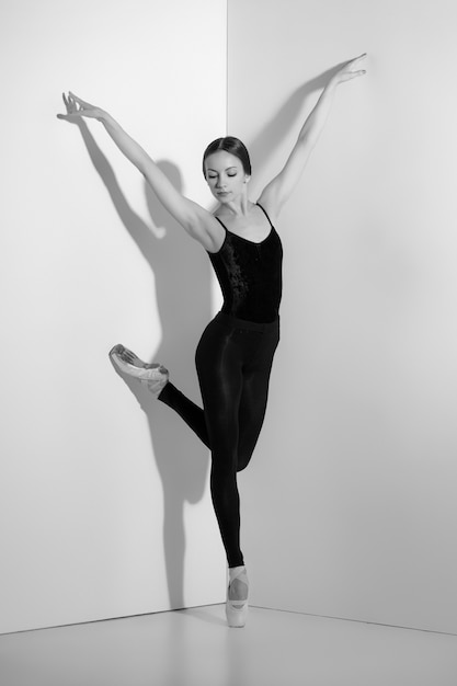 Ballerine En Tenue Noire Posant Sur Des Pointes, Fond De Studio. Photo gratuit