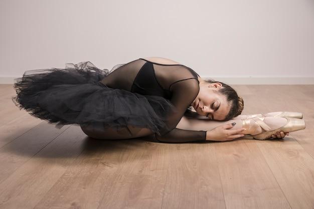 Ballerine vue de côté tenant ses jambes Photo gratuit