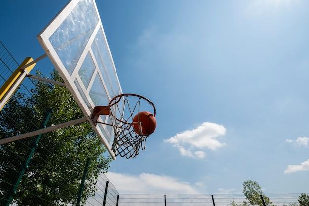 Ballon de basketball dans un cerceau à faible angle de vue Photo gratuit
