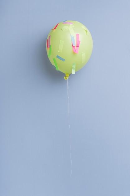 Ballon Avec Des Confettis Sur Fond Bleu Photo gratuit
