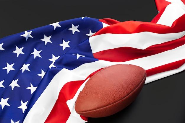Ballon de football américain et drapeau américain sur la table se bouchent Photo Premium