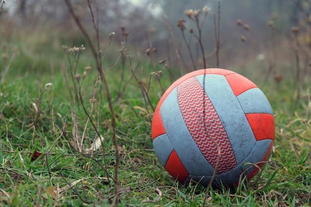 Ballon De Football Rouge-blanc Sur L'herbe Dans Un Parc Avec Temps Pluvieux Sombre Et Brumeux. Photo Premium