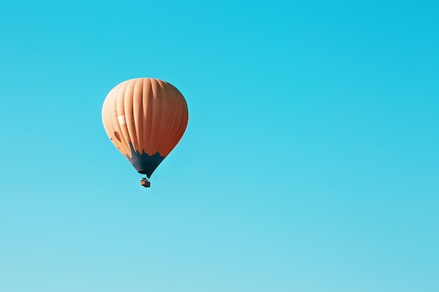 Le Ballon Orange S'envole Contre Le Ciel Bleu Photo Premium