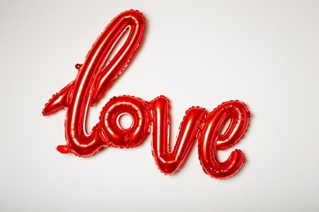 Ballon Rouge Avec Le Mot Amour En Aluminium Sur Fond Blanc. Photo Premium