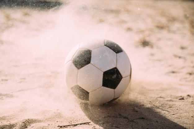 Ballon de soccer et particules de sable Photo gratuit