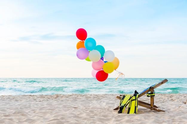 Ballons à air chaud colorés sur une plage tropicale Photo Premium