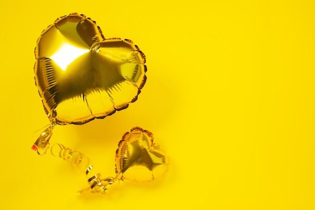 Ballons En Aluminium Jaune En Forme De Coeur Sur Jaune Photo Premium
