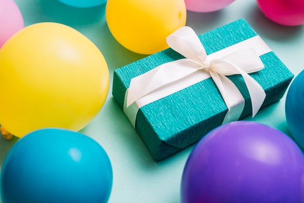 Ballons colorés autour de la boîte-cadeau attachés avec un ruban blanc Photo gratuit