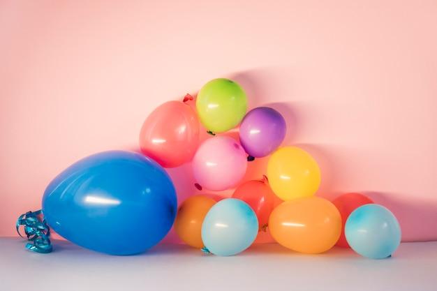 Ballons colorés sur fond rose Photo gratuit