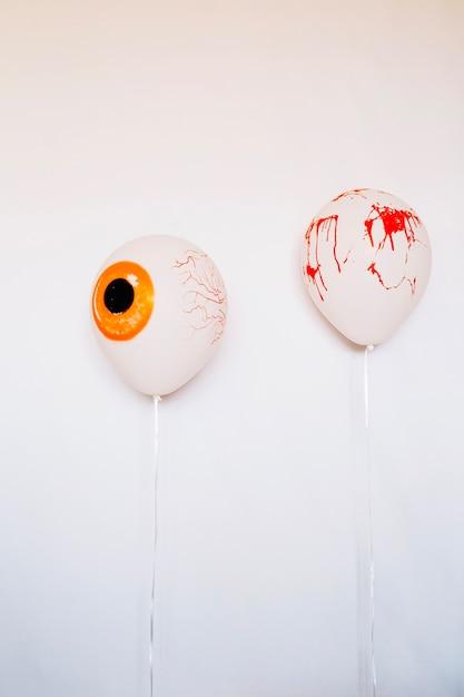Ballons effrayants avec du sang sur le mur blanc Photo gratuit