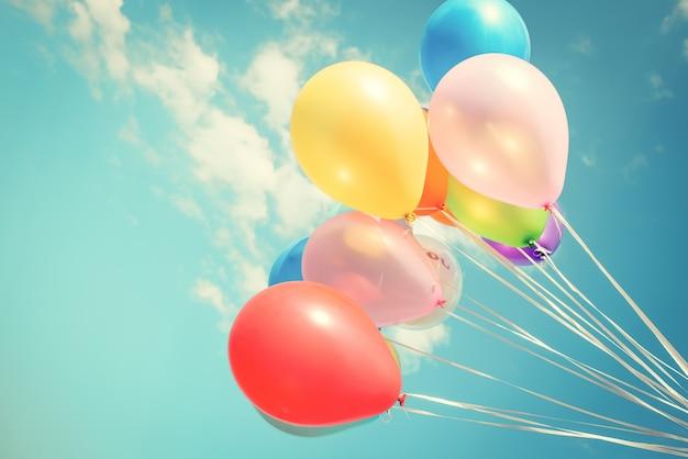 Ballons de fête colorés sur ciel bleu avec un effet de filtre instagram vintage rétro. Photo Premium