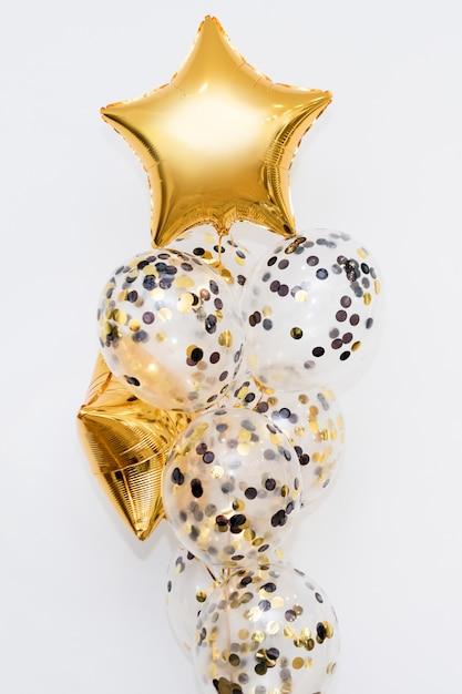 Ballons à l'hélium or métallique de différentes formes sur fond blanc. concept de décoration de vacances et d'anniversaire Photo Premium