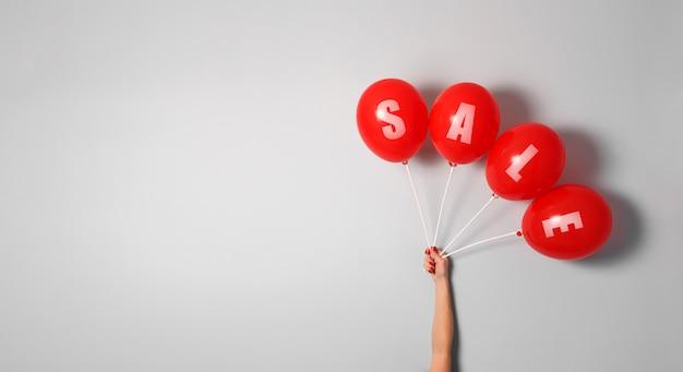 Ballons rouges avec signe de vente dans la main de la femme avec un espace copie pour votre texte Photo Premium