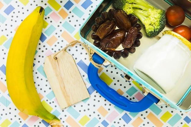 Banane allongée près de la boîte à lunch Photo gratuit